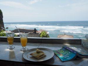 Tousty, dva drinky s plastovým brčkem a výhled na moře.