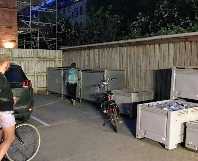 Záběr na roh parkoviště u supermarketu s kontejnery, na obrázku jsou dva lidi a dvě kola, dívka s batohem jde směrem ke kontejneru.