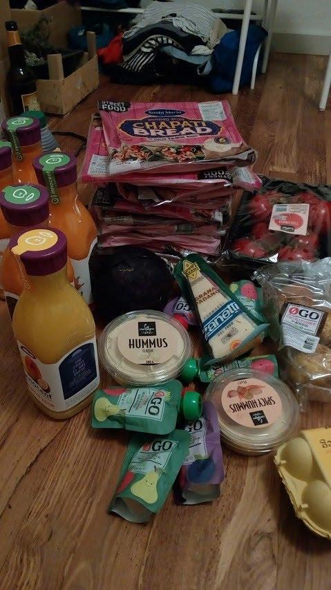 hromada jídla - džusy, hummus, parmezán, přesnídávky, rajčata, čapati chleba