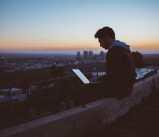 Muž pracující na laptopu. Zdroj: Unsplash na římse výškové budovy